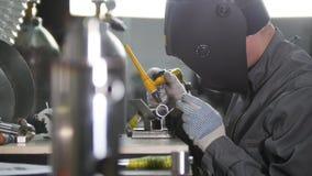 промышленное изготавливание Работник человека на ткани Делающ разрезы в трубке утюга стоковые изображения