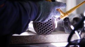 промышленное изготавливание Работник человека на ткани Деталь утюга с маленькие отверстия в нем стоковая фотография