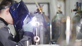 промышленное изготавливание Сварщик человека работая на ткани Деталь утюга с маленькие отверстия в нем Процесс заварки стоковое изображение rf
