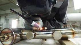 промышленное изготавливание Человек работая с деталью трубы утюга Процесс заварки стоковое фото rf