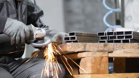 промышленное изготавливание Человек работая с деталью утюга Зашкурить процесс стоковое изображение rf