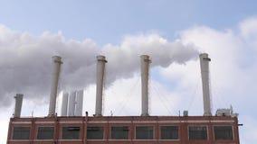 Промышленное место с куря трубами с голубым небом на предпосылке акции видеоматериалы