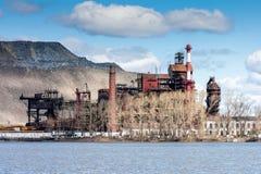Промышленное предприятие около озера против фона огромного сброса Стоковое фото RF