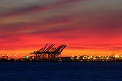 промышленно над гаван заходом солнца Стоковые Фото