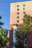 Промышленные альпинисты красят стену и фасад жилого дома мульти-этажа на большой возвышенности стоковое фото rf