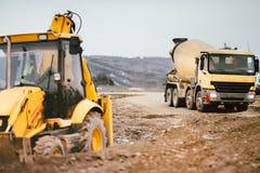 Промышленные машинное оборудование экскаватора backhoe и тележка цемента на месте строительства дорог стоковая фотография