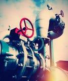 Промышленные стальные трубопроводы и клапаны против голубого неба Стоковые Изображения