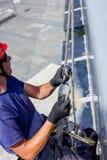 Промышленный альпинист подготавливает, регулирует его веревочки стоковая фотография rf
