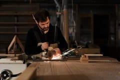 Промышленный инструментальный металл работника плотника с много острых искр на стенде работы в мастерской плотничества Фокус выбо стоковые изображения rf
