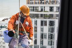 Промышленный мойщик окон альпиниста в оранжевых форме и шлеме Стоковая Фотография RF