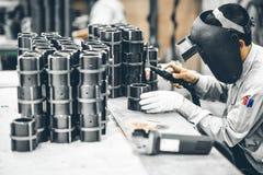Промышленный работник в промышленном предприятии меля для того чтобы закончить трубу металла Стоковая Фотография