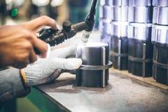 Промышленный работник в промышленном предприятии меля для того чтобы закончить трубу металла Стоковое Изображение RF