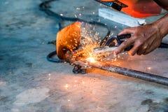 Промышленный работник используя машину сварщика сваривает инструмент лопаты Стоковые Фотографии RF