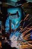Промышленный работник сваривает сливающ автомобильную деталь в фабрике автомобиля Стоковая Фотография RF