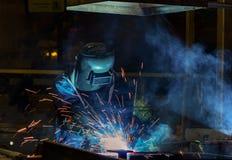 Промышленный работник сваривает часть металла ремонта в фабрике автомобиля Стоковое Изображение