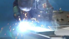 Промышленный работник с элементами inox заварки защитной маски в стальных структурах изготовляет мастерскую место Заварка  сток-видео