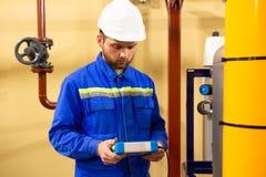Промышленный работник техника в шлеме с инструментом для измерения стоковая фотография rf