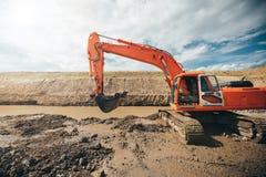 Промышленный экскаватор работая во время earthmoving работает на строительной площадке шоссе Детали конструкции Стоковые Изображения