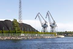 2 промышленных краны и кучи угля Стоковая Фотография RF