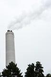 Промышленная печная труба с дымом с деревом в фронте Стоковое Изображение