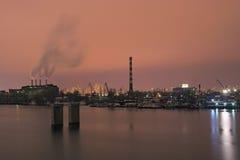 Промышленная часть города фабрика работает на ноче Дым приходит от печных труб Стоковые Изображения