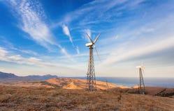 Промышленный ландшафт при ветротурбина производя электричество в горах на заходе солнца стоковые фотографии rf