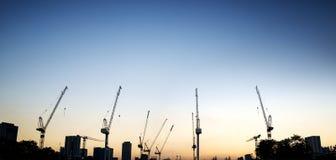 Промышленный ландшафт с силуэтами кранов на предпосылке захода солнца Стоковое Изображение