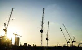 Промышленный ландшафт с силуэтами кранов на предпосылке захода солнца Стоковая Фотография