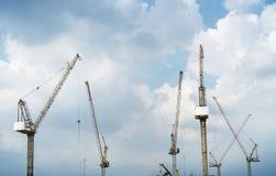Промышленный ландшафт с силуэтами кранов на предпосылке захода солнца Стоковые Фото
