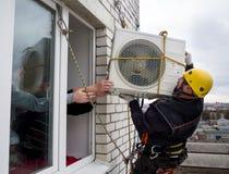 Промышленный альпинист устанавливает кондиционер воздуха на стене блока квартир Стоковое фото RF