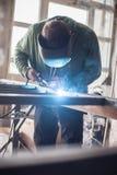 Промышленный сварщик работая металл заварки с защитной маской Стоковые Изображения