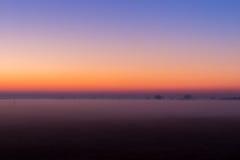 Промышленный туманный ландшафт, силуэт старой фабрики против неба захода солнца и туман на голубом часе на ноче Стоковое Изображение RF