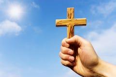 Проповедник держа деревянный крест против голубого неба Стоковая Фотография RF