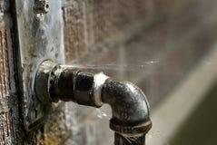 Пропускающая влагу труба с Squirting воды распыляя вне стоковое фото rf