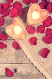2 просвещенных свечи в в форме сердц подсвечниках с подняли Стоковое фото RF