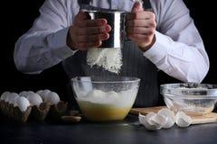 Просеивать муку на темной предпосылке рецепт пирога или торта делая концепцию стоковые изображения