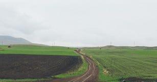 Проселочная дорога в середине полей стоковое изображение