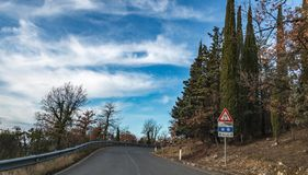 Проселочная дорога европейской страны Поверните справедливо, дорожный знак, деревья и яркое голубое небо Асфальт и сухая трава Стоковое Фото
