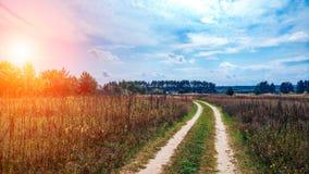 Проселочная дорога и поля лета на предпосылке голубого красивого облачного неба и красивом расстоянии леса шоссе _ Стоковая Фотография
