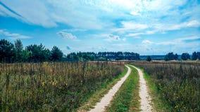 Проселочная дорога лета и предпосылка полей голубого красивого облачного неба и красивое расстояние леса шоссе _ Стоковые Изображения