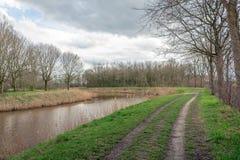 Проселочная дорога с следом тележки вдоль узкого реки стоковые изображения