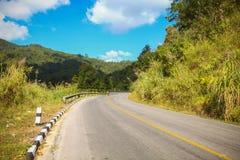 Проселочная дорога бежать через зеленые поля Дорога замотки Стоковая Фотография