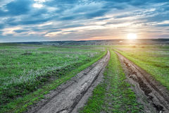 Проселочная дорога в зеленом поле на заходе солнца стоковое фото rf