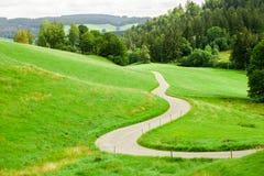 Проселочная дорога замотки между зелеными полями в горах Стоковые Изображения