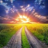 Проселочная дорога и заход солнца Стоковое фото RF