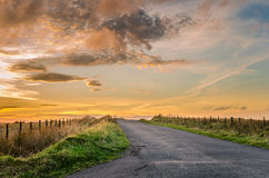Проселочная дорога на заходе солнца Стоковые Изображения