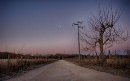 Проселочная дорога с waning луной Стоковые Изображения