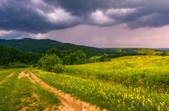 Проселочная дорога через сельские поля в ландшафте лета гор Стоковая Фотография