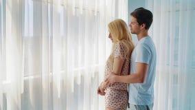 Просигнальте внутри молодого человека обнимая белокурую женщину от позади в утре дома акции видеоматериалы