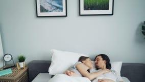 Просигнальте внутри молодых людей лежа в обнимать кровати целуя лаская дома сток-видео